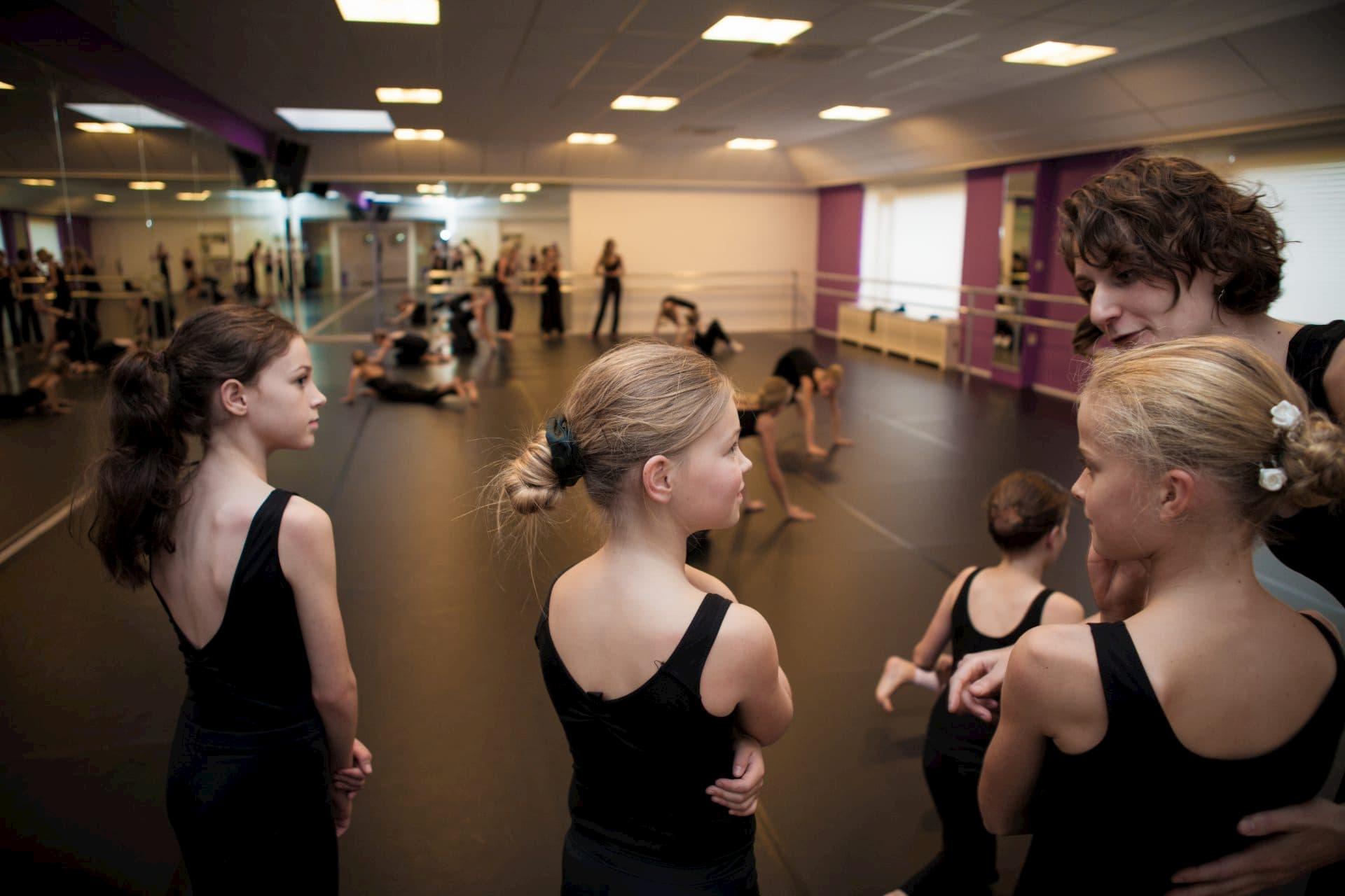 Balletschool Heerhugowaard dansles dans les geven zwarte pakjes leerlingen juf dansjuf uitleggen danszaal